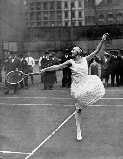 Сюзанн Ленглен — французская теннисистка, чьим именем сейчас назван один из основных кортов на турнире Ролан Гаррос. Поговаривают, что она пила и курила как сапожник прямо на корте, а в теннис играла совсем не по-женски. Однако именно Сюзанн была бессменной чемпионкой Уимблдона с 1919 по 1926 гг. Наряды на каждый турнир ей шил кутюрье Жан Пату. Пату стал первым дизайнером, представившим линию спортивной одежды для женщин. Она включала теннисные юбки и шорты, трикотажные купальные костюмы. Известно, что Пату одевал Сюзанн не только на теннисных кортах.