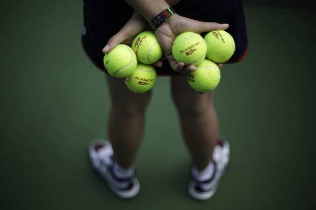 """Фото: Боллбой держит в руках во время US Open 2013 """"женские"""" мячи с красным лого / David Goldman/AP"""